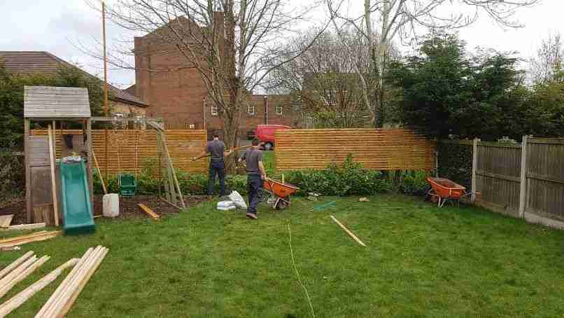 Acorn Gardening staff building a wooden slatted fence