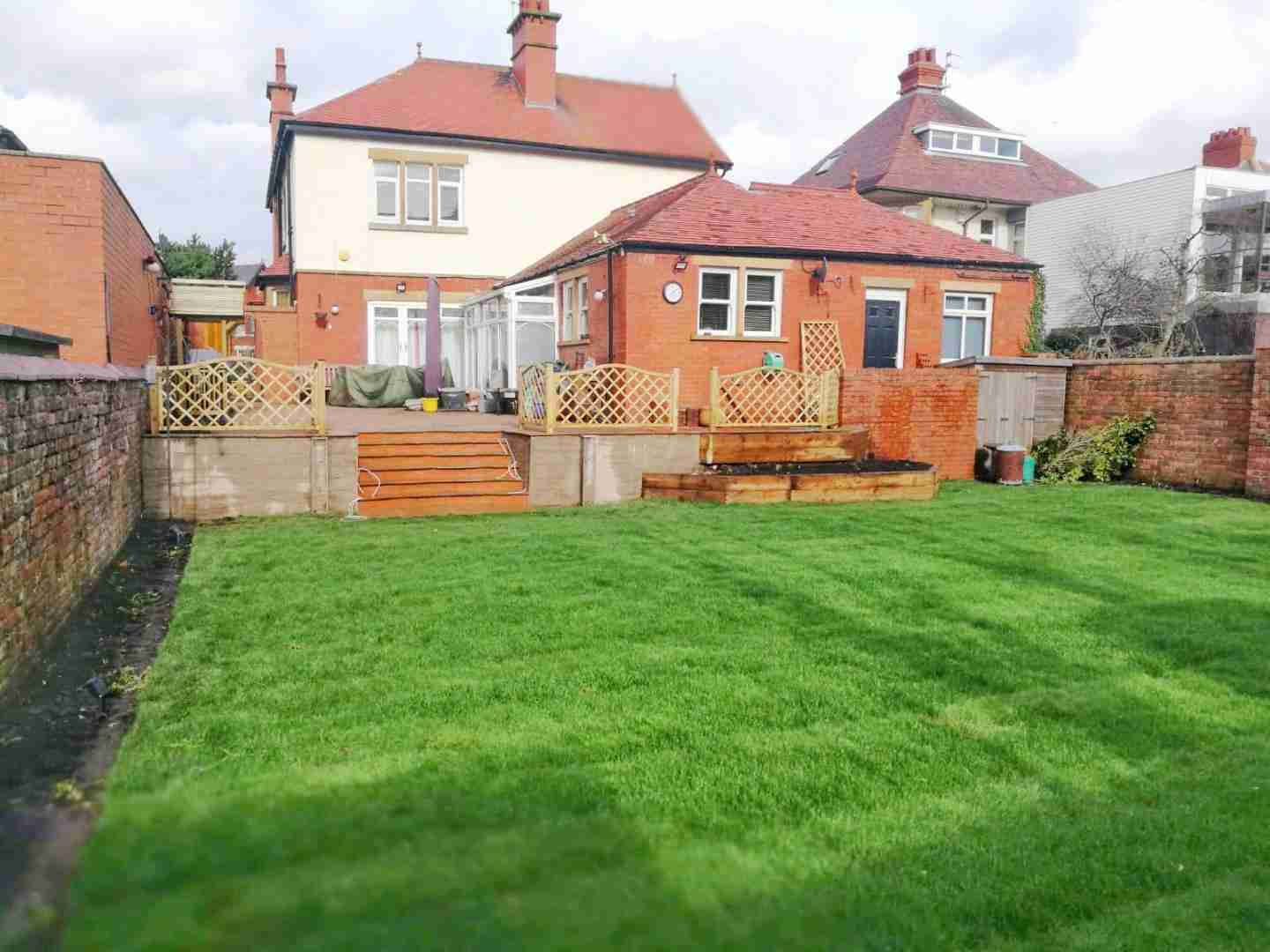 Large turf area with stone steps leading to block paving area. Landscape gardening, landscape design, Acorn Gardening