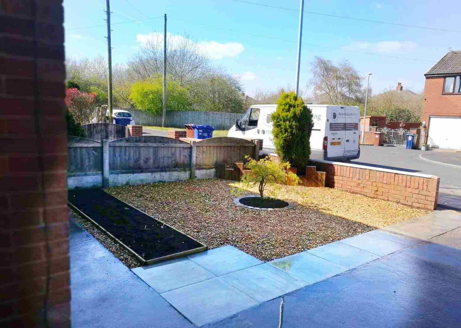 A small garden with a new flower bed, flint gravel, new drainage and a custom built raised bed at the back