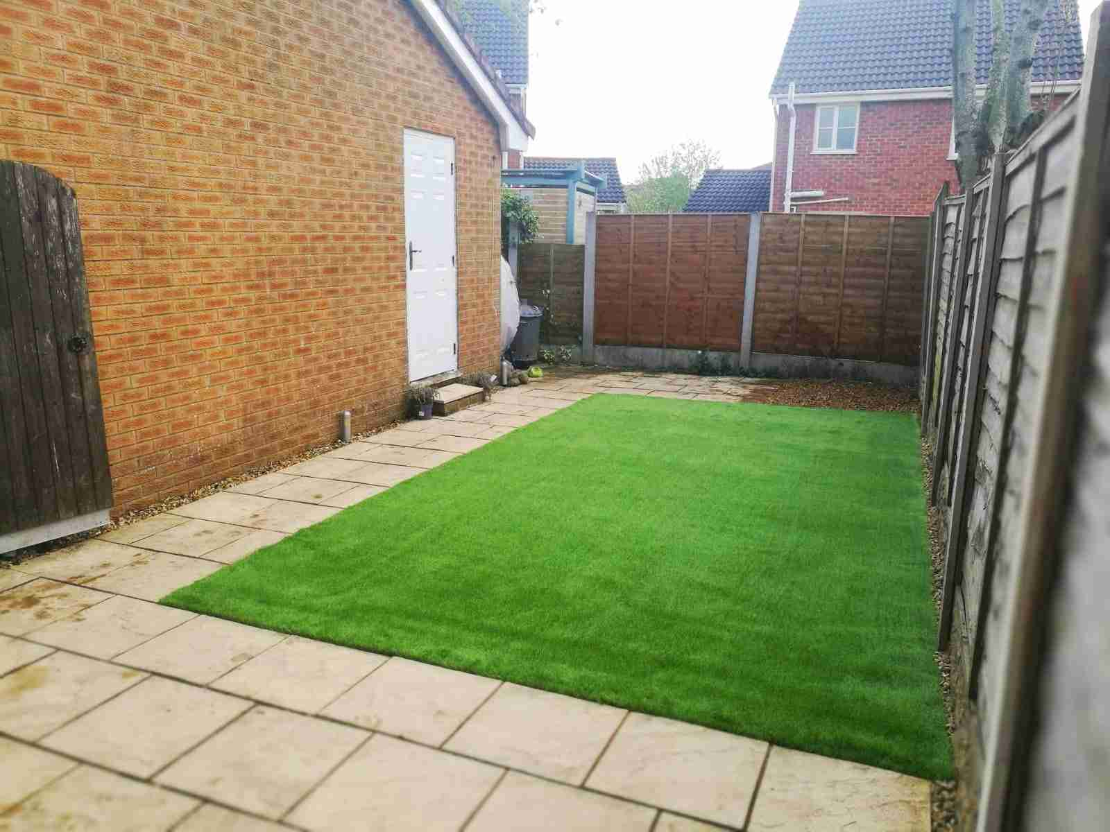 Square of artificial grass surrounded by paving