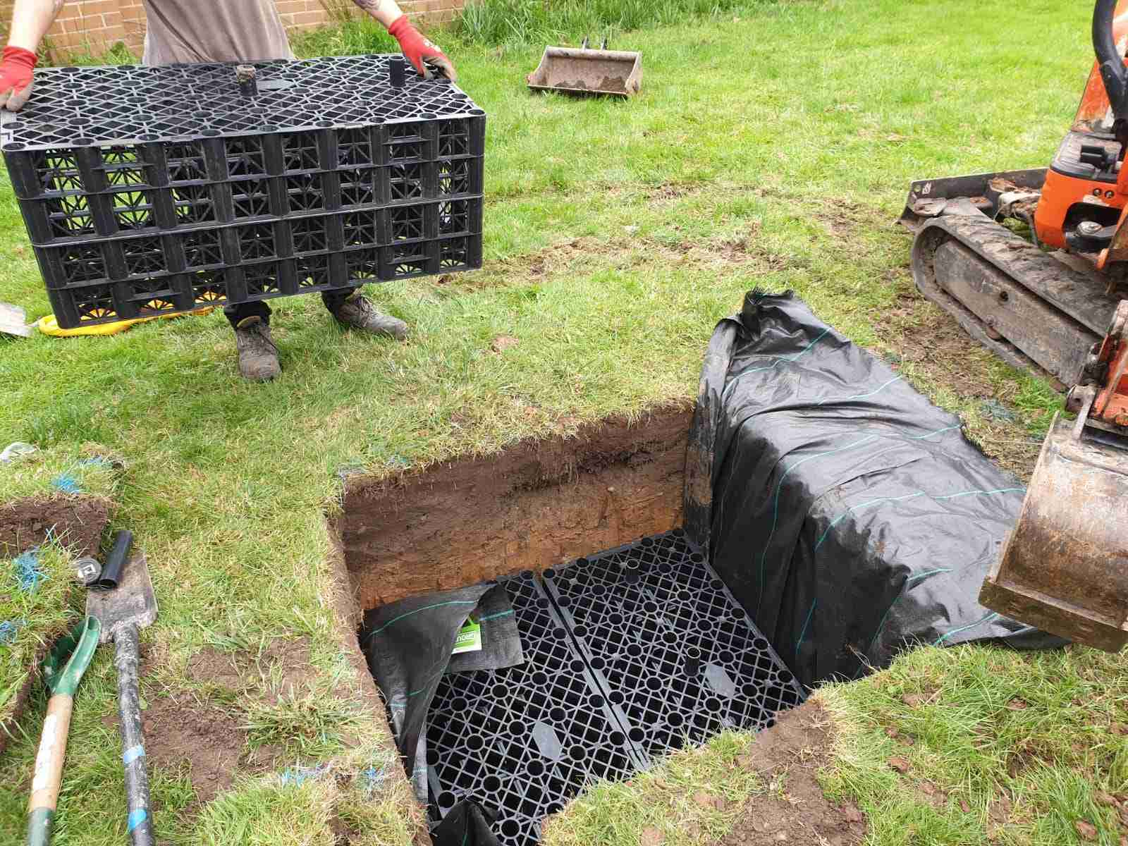 Square hole in garden filled with drainage cubes