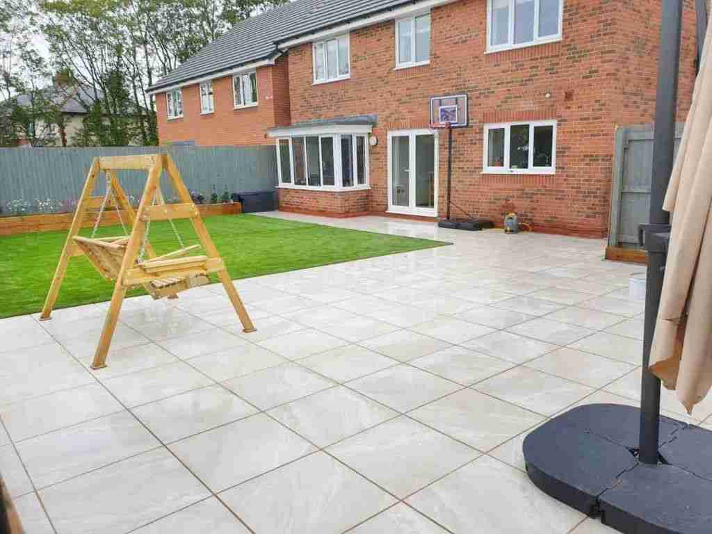 A large garden in a new build house with white porcelain paving and artificial grass. Showing the landscaping work of Acorn Gardening
