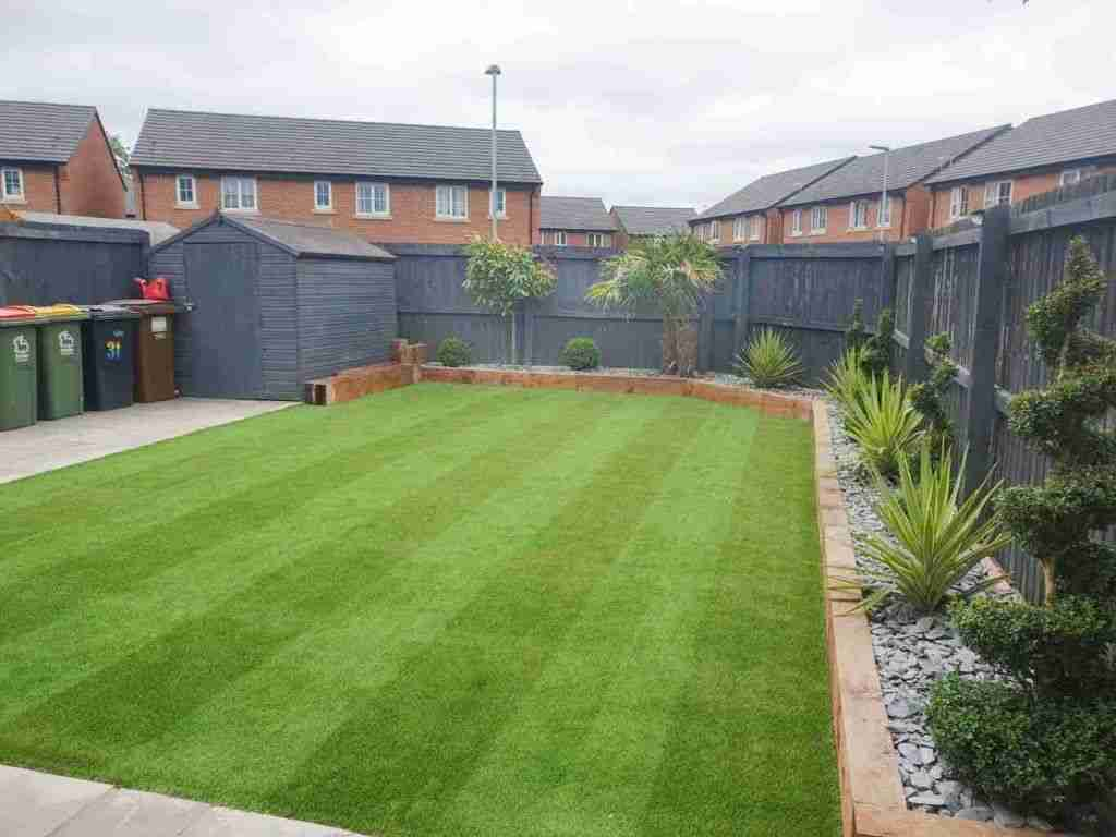 Large low maintenance garden with striped artificial grass, wooden sleeper borders and styled plants