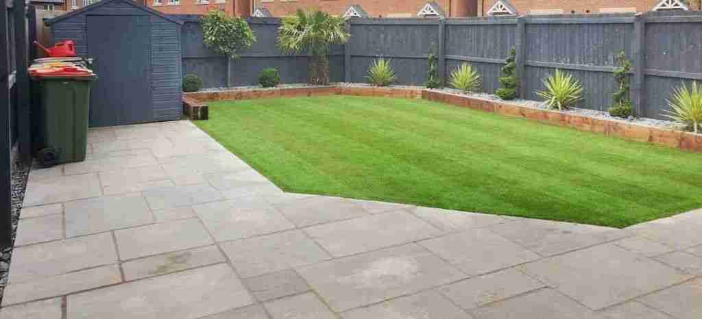 Low mainteance garden with houses in the background. A grey fence is surrounding a slate planting area with wooden boarders. The lawn is bright green artificial grass with stripes,