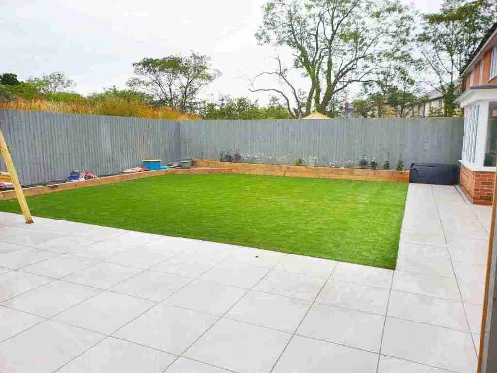White porcelain paving with artifical gerass and wood sleep border, back yard landscaping