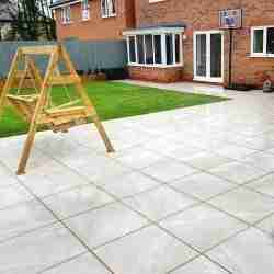 White warble effect porcelain paving with grass in the background