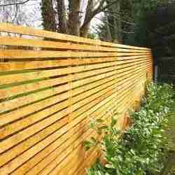 bown stained slatted wooden fence next to a hedge