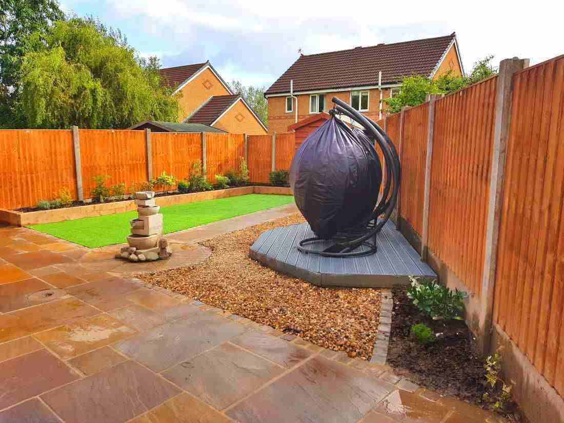 New landscape gardening work in Fullwood, Preston. A fenced garden with hanging chairs, decking, artificial grass and paving