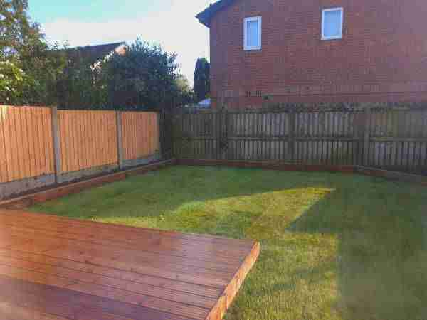 Full view of a landscape gardening project in Penwortham by Acorn Gardening. You can see a square of wooden decking, some wooden sleeper flower beds and newly laid turf