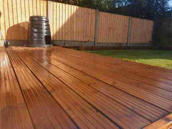 Close up shot of new soft wood decking and a new wooden slatted fence