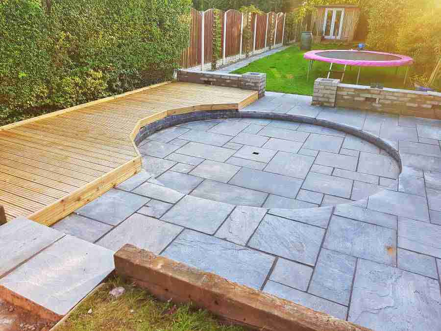 Grey sand stone paving area with light wood decking and a stone circle