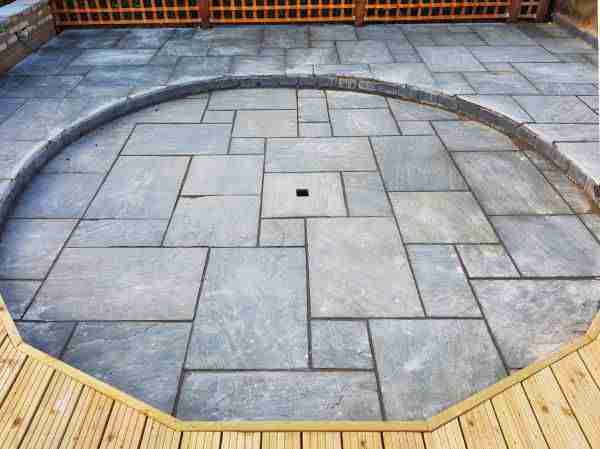 Circle of paving dipped into the ground with wooden decking on one side. Landscape gardening, Preston