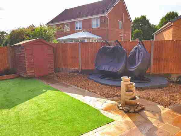 Small garden with decking and handing chairs. Landscape gardening work by Acorn Gardening Preston