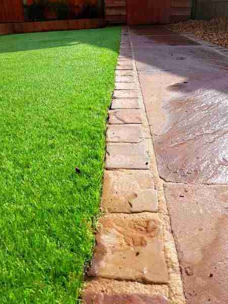 Close up shot of a stone block border between artificial grass and Indian stone paving