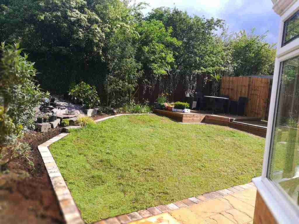 Back garden with wooden decking, water feature and paving