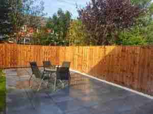 Dark porcelain paving with a border of white pebbles and a new wooden fence. This is some landscaping work we completed in September.