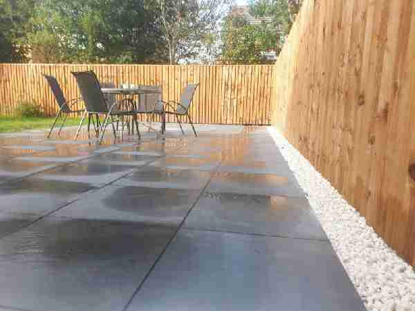 close up shot of landscaping work in penwortham. Showing a dark porcelain paving are, white pebbles and a new wooden fence