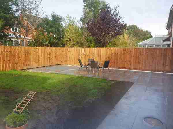 Landscape gardening work in Penwortham. Dark porcelain paving with a white pabble border and a new wooden lap panel fence