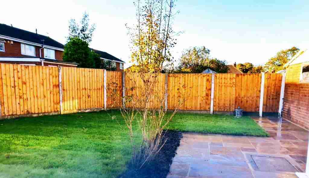 Side on view of a newly landscaped garden in Penwortham. The garden has a new fence, turf and paving.