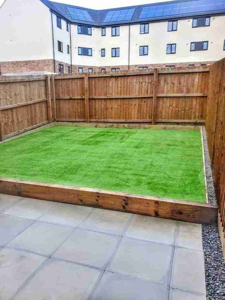 Landscape gardening work in Buckshaw Village, Preston. The work includes an artificial grass area, concrete paving and a wooden fence