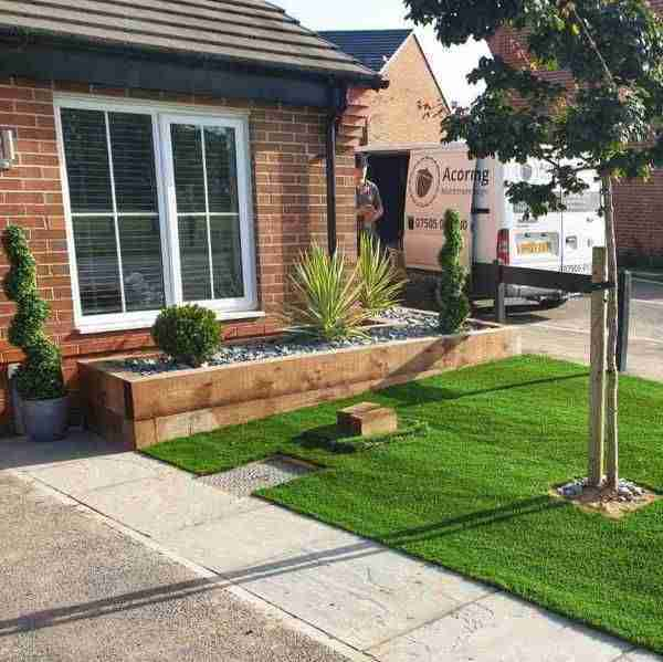 Front garden landscaping with artificial grass and raised wooden sleeper borders