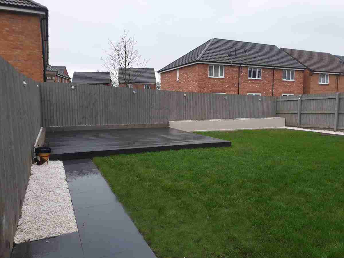 Charcoal porcelain paving, while gravel and composite decking. Landscaping Preston