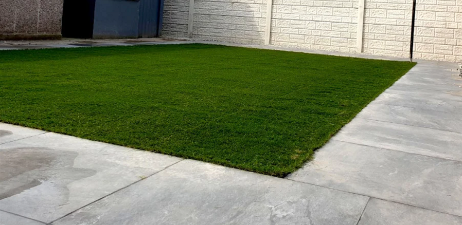 Artificial grass edged with porcelain paving