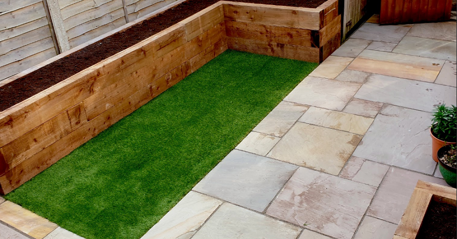 Artificial grass edged with a sleeper border and sandstone paving