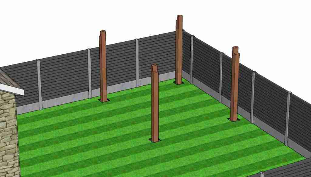 Wooden posts setting in the ground as pergola legs