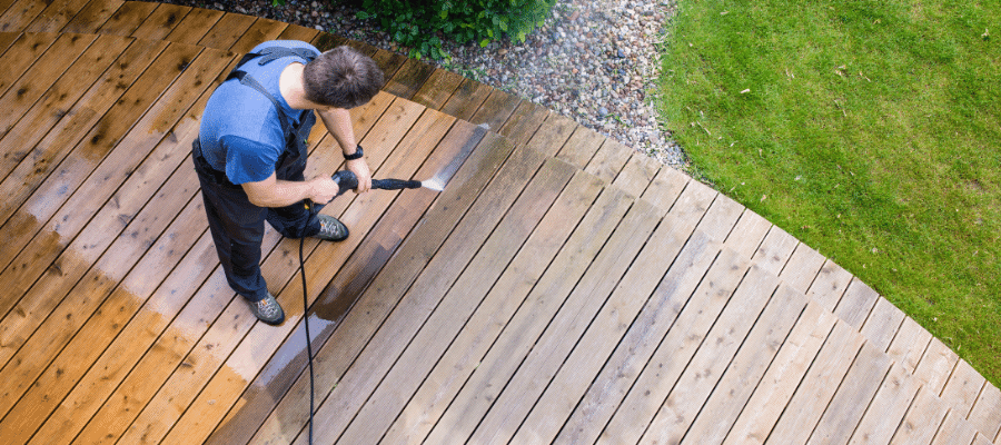 Man cleaning decking with a power washer