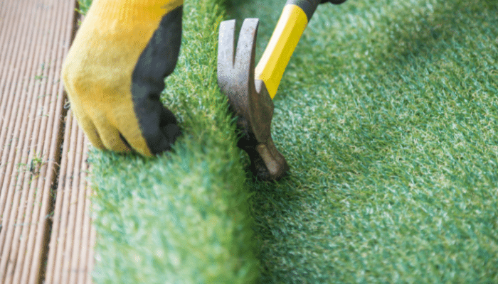 Artificial grass being laid on decking