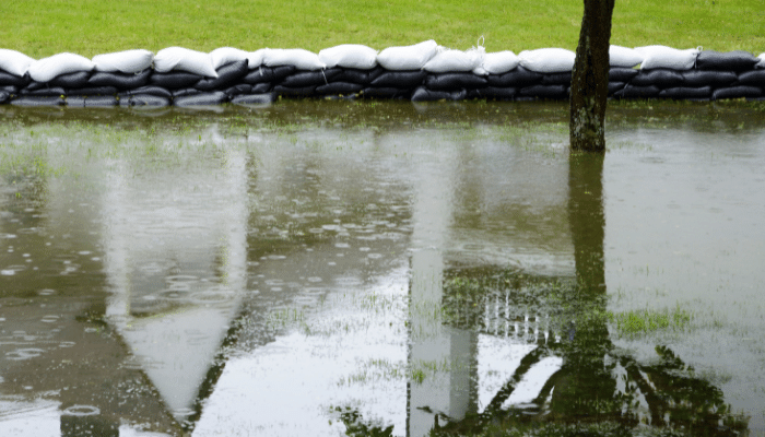 Flooded garden with sandbags keeping in large pool of water