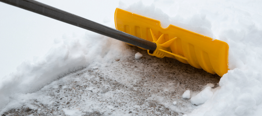 removing snow and ice from decking with snow shovel