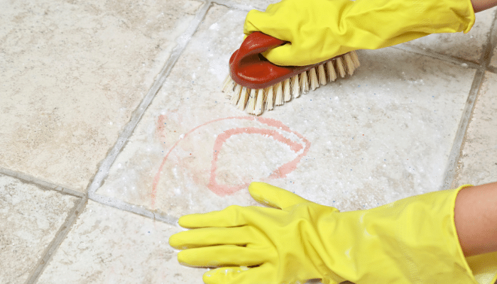 Scrubbing stone paving with a brush by hand