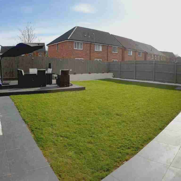 Composite decking with chairs and green lawn