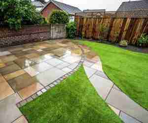 sawns sandstone paving and artificial grass by acorn gardening