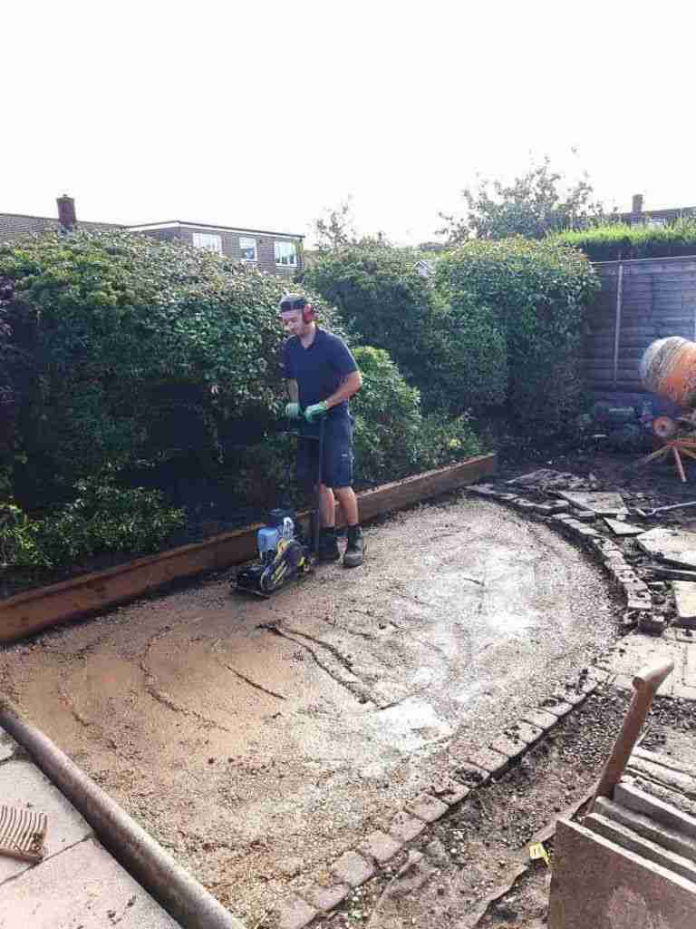 Compressing paving foundations with a whacker plate