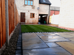 Indian stone paving, block stone borders, turf, lap panel fencing, river gravel