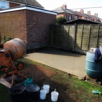 Mixing cement for a concrete shed base on a landscaping project in Preston