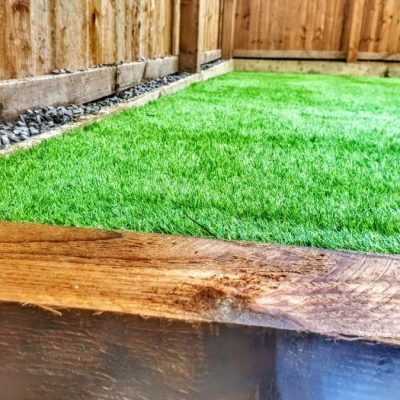 Close up shot of some landscaping work in Buckshaw village. The photo includes artificial grass, wooden sleepers, gravel and fencing