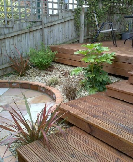 Stepped wooden decking in a small back yard with plants in a gravel area