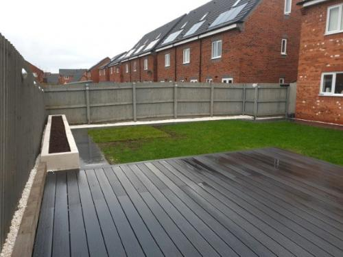 White rendered flower bed, black composite decking and porcelain paving. Acorn Landscape Gardening